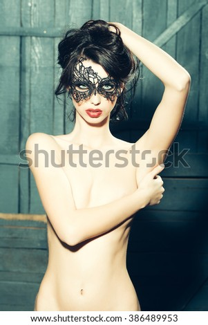 Attractive mysterious sexy young sensual woman with brunette hair in lace black mask looking forward standing topless with hand on bare chest in studio on wooden background, vertical picture - stock photo