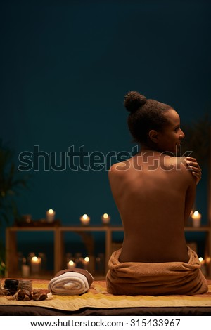 Attractive naked African-American woman in luxury spa salon, view from the back - stock photo