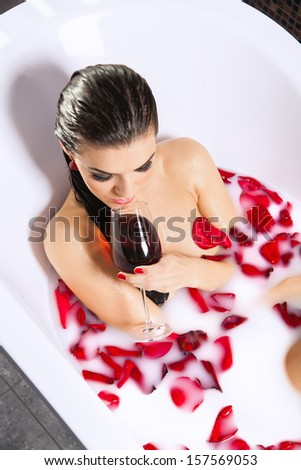 Attractive naked girl enjoy a glass of wine in bath with milk and rose petals. Spa treatments for skin rejuvenation and full relaxation - stock photo