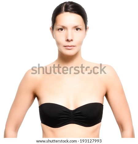Attractive naked slim young woman wearing a black strapless bra standing looking directly at the camera with a serious expression, isolated on white - stock photo
