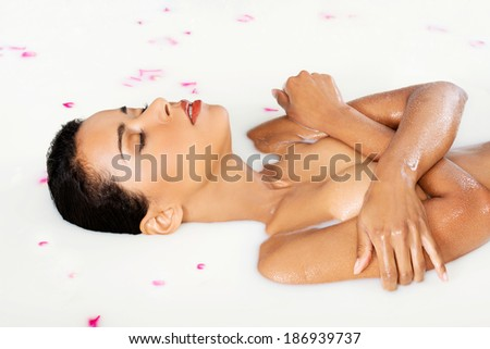 Attractive naked woman lying in a milk bath. With rose petal. Up front view. - stock photo