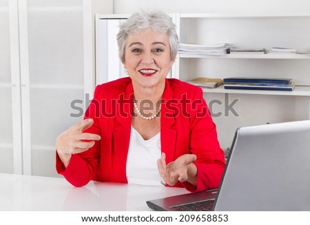 Attractive older smiling senior businesswoman sitting at desk wearing red jacket and explain something. - stock photo