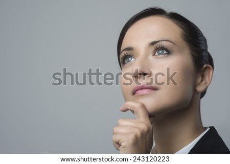 Attractive pensive business woman with hand on chin looking away. - stock photo