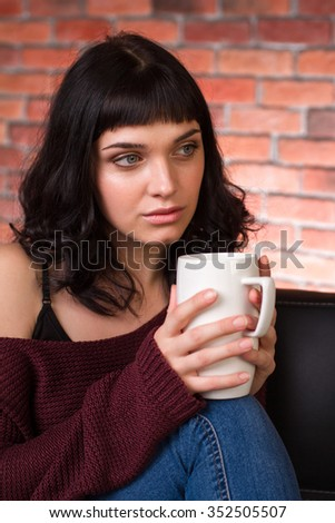 Attractive pensive young woman in sweater and jeans sitting and drinking tea over brick wall background - stock photo