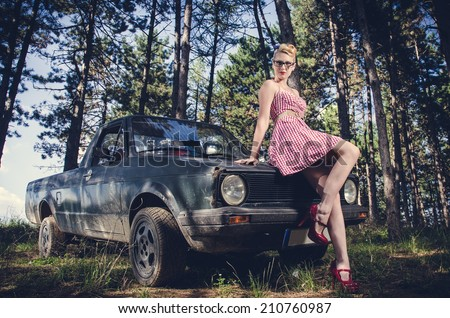 Attractive pin-up girl in short dress posing next to retro pickup car - stock photo