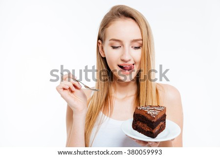 Attractive playful young woman holding and eating piece of chocolate cake over white background - stock photo