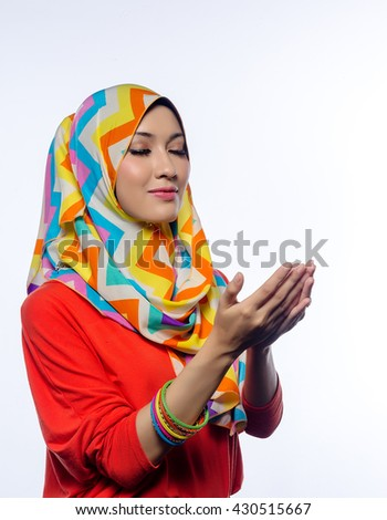 Attractive portrait of young muslim woman in head scarf smile, spreads out hands while praying - stock photo