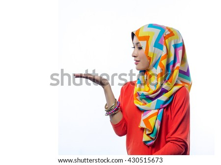 Attractive portrait of young muslim woman looking at her palm - stock photo