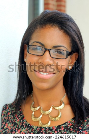 Attractive Professional African American Business Woman Person Black Hair Wearing Glasses and Smiling and Wearing a Necklace  - stock photo