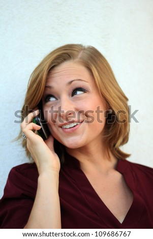 Attractive Professional Business Woman Smiling and On the Phone While Looking to the Side - stock photo