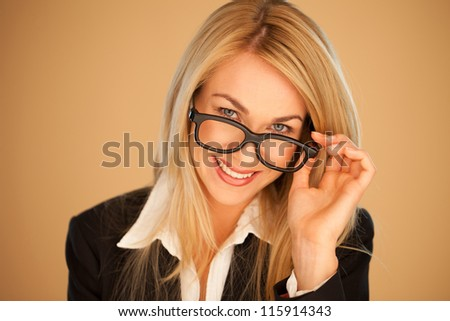 Attractive professional woman peering over the top of her glasses with a lovely smile - stock photo