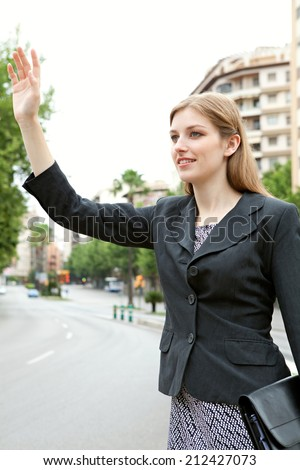 Attractive professional young business woman standing in a financial city street calling a taxi and holding up her arm. Business people commuting and using public transport to get to work. - stock photo