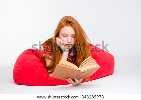 Attractive redhead concentrated girl lying and relaxing in red bean bag and reading a book isolated on white background - stock photo