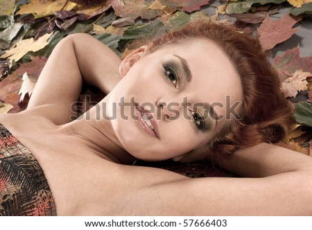 Attractive redhead in autumn leaves - stock photo