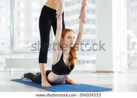 Attractive redhead young woman doing stretching exercises with personal trainer  - stock photo