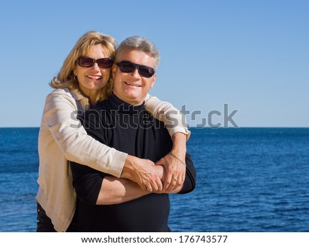 Attractive romantic middle-aged mature man and woman wearing sunglasses standing in the sunshine enjoying the seaside in an affectionate embrace - stock photo