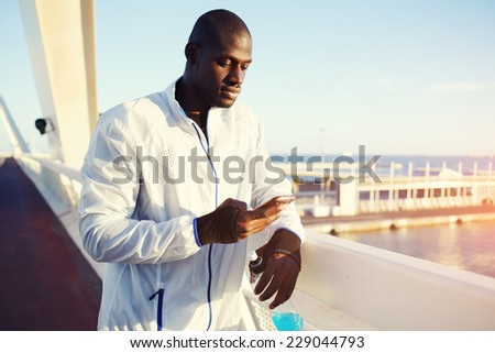 Attractive runner using mobile phone after fitness training, attractive sportsman in white windbreaker typing something on his mobile smart phone standing at sunset on beautiful road - stock photo