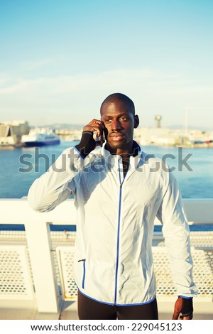 Attractive runner using mobile phone after fitness training, dark skinned sportsman with cell phone standing on beautiful sea port background - stock photo
