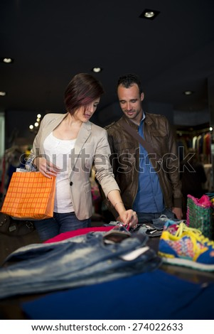Attractive 30s couple at clothes store choosing clothes - stock photo