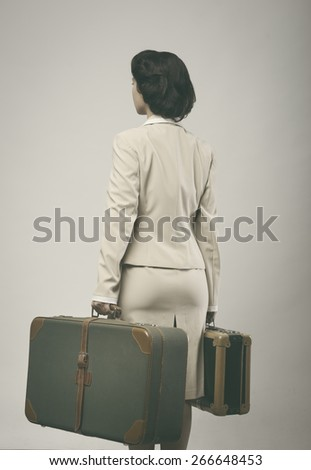 Attractive 1950s style woman holding suitcases rear view. - stock photo