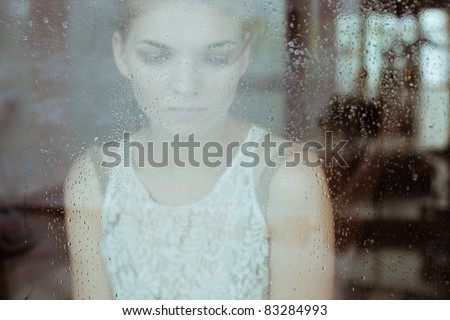 Attractive sad girl standing at the window watching the rain - stock photo