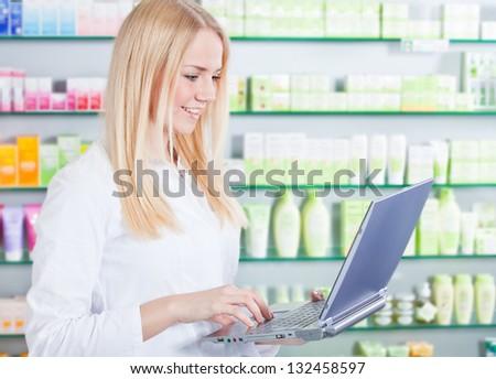 Attractive saleswoman in pharmacy using laptop. - stock photo