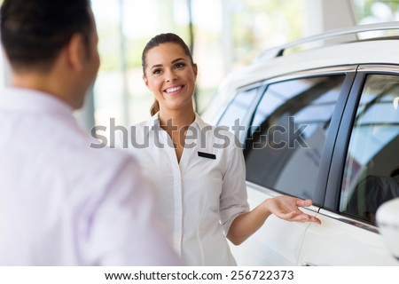attractive saleswoman showing new car to a customer in showroom - stock photo