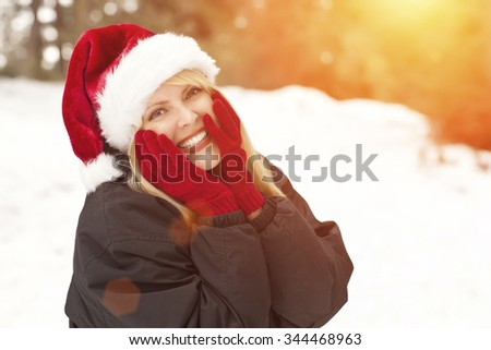 Attractive Santa Hat Wearing Blond Woman Having Fun in The Snow on a Winter Day. - stock photo
