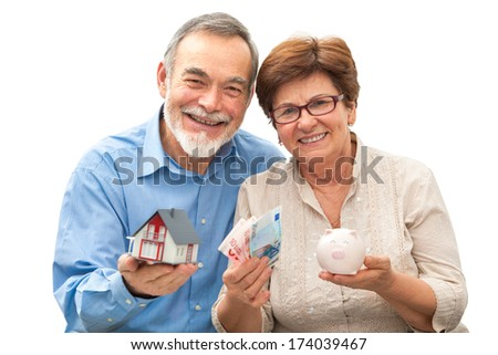 attractive senior couple holding a house model and piggy bank - stock photo