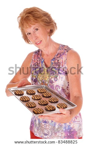 attractive senior with tray of cookies on a white background - stock photo
