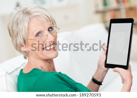 Attractive senior woman using a tablet computer relaxing on a sofa at home turning to smile at the camera - the screen blank is visible to the viewer - stock photo