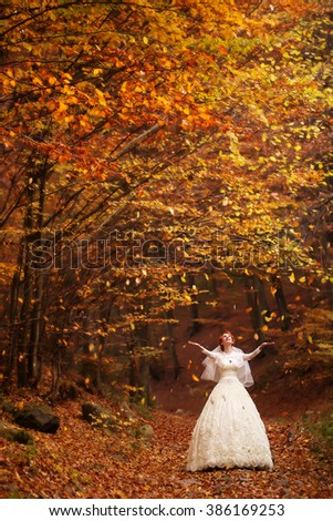 Attractive sensual bride young woman in beautiful white long wedding dress standing in deep autumn forest outdoot on natural background, vertical picture - stock photo