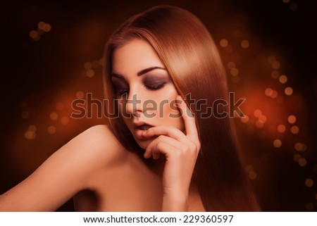 Attractive sensual brown hair woman with closed eyes in studio on abstract dark background - stock photo