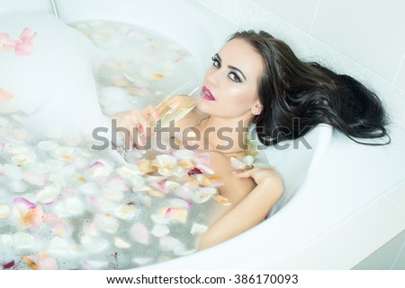 Attractive sensual brunette young woman with long wet hair and bright makeup holding wine glass lying in bath tub full of water with foam and rose flower petals, horizontal picture - stock photo