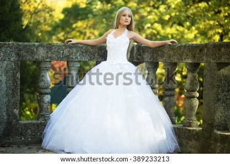 Attractive sensual thoughtful young bride girl with long blonde hair in white wedding dress standing outdoor near stone fence on natural background, horizontal picture - stock photo