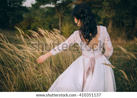 Attractive sensual young brunette bride in white wedding dress and long veil standing in field - stock photo