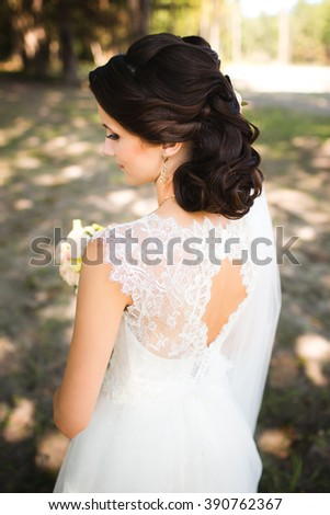 Attractive sensual young brunette bride in white wedding dress and long veil standing in forest holding bouquet outdoor on natural background. Sensual photo of bride's back - stock photo