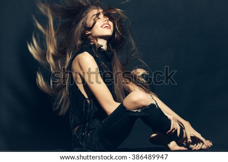 Attractive sensual young fashionable woman in stylish cloth and torn jeans with long beautiful hair sitting indoor on studio background, horizontal picture - stock photo