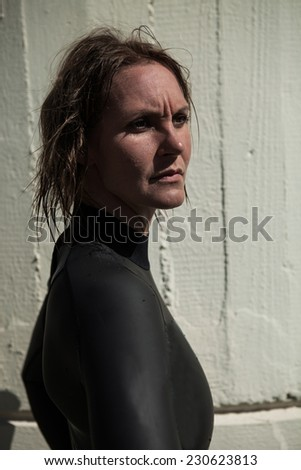 Attractive serious looking brunette female swimmer wearing black wetsuit with wet hair and sunlight in face - stock photo
