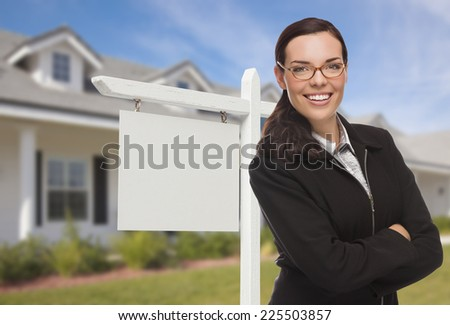 Attractive Serious Mixed Race Woman In Front of House and Blank Real Estate Sign. - stock photo