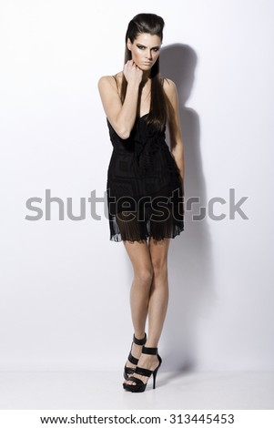 attractive sexy fashion model with natural brunette hair, long legs, full lips, perfect skin posing in studio, wearing black shoes and transparent cocktail dress, beauty photoshoot, retouched image - stock photo