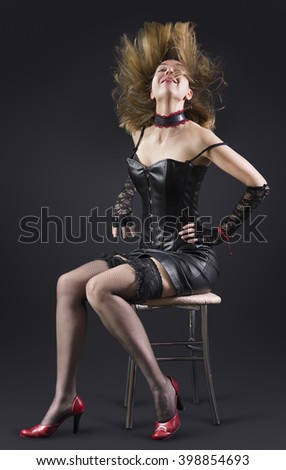 Attractive sexy girl in black corset, black lace gloves and black lingerie is sitting on chair. Her brown hair is flying up like a flame. Studio shooting. - stock photo