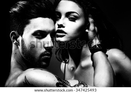 Attractive sexy woman leaning on the bare chest of attractive young brunette man. Fashion photo. - stock photo