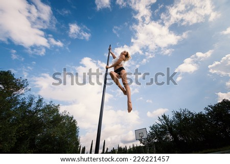 Attractive sexy woman pole dancer performing outdoors against blue cloudy sky. - stock photo