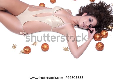 Attractive sexy woman with shine gold bikini lying on her back there are Christmas balls around her - stock photo