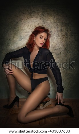 Attractive sexy young woman in black shirt and panties sitting on a pile of books on the floor. Sensual redhead with long legs on high heels shoes shoes posing provocatively against gray wall - stock photo
