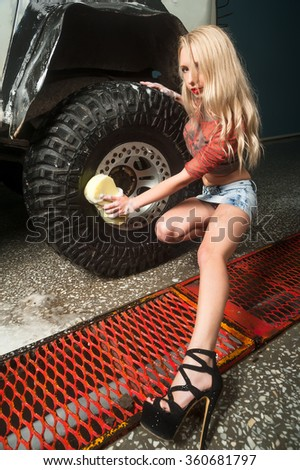 Attractive sexy young woman washes offroad car by foam hose - stock photo