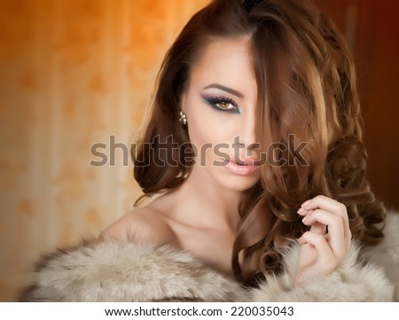 Attractive sexy young woman wearing a fur coat posing provocatively indoor. Portrait of sensual female with creative makeup, studio shot. Beautiful girl covered only with a fur exposing her shoulders - stock photo