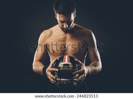 Attractive shirtless football player holding protective helmet and posing - stock photo