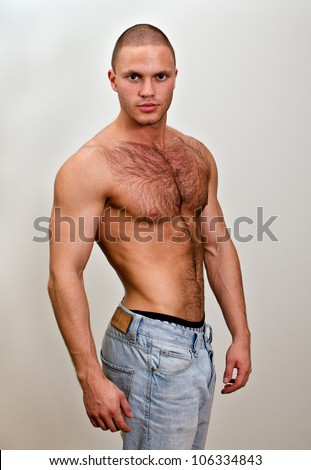 Attractive shirtless male in jeans, on grey background - stock photo